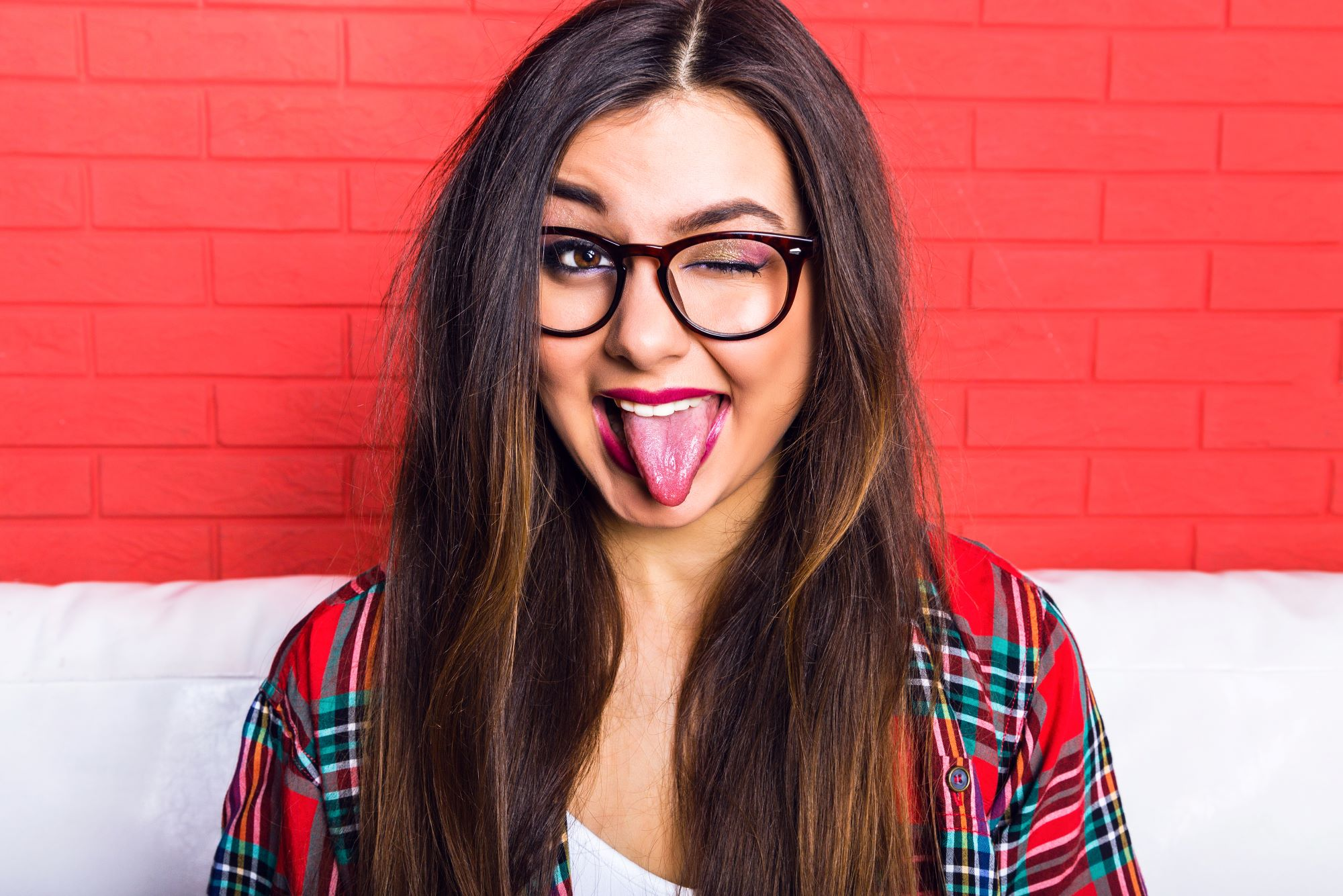 Girl in red plaid shirt sticking out her tongue to show what your tongue can tell you about your health